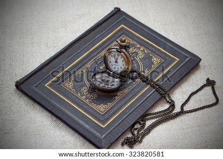 vintage still life with pocket watch and old book - stock photo