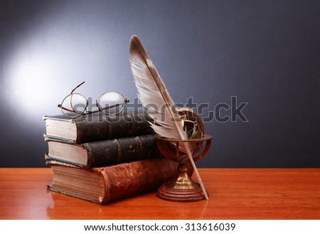 Vintage still life with quill pen near book and spectacles on dark background - stock photo