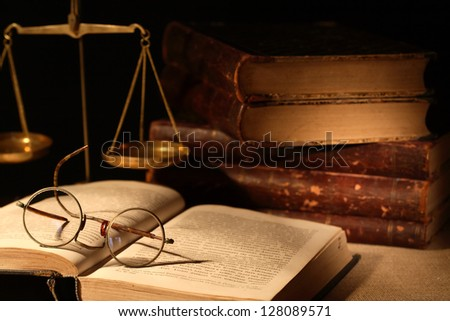 Vintage still life with spectacles on open book near brass weight scale on dark background - stock photo