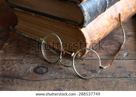 Vintage still life with stack of old books near spectacles - stock photo