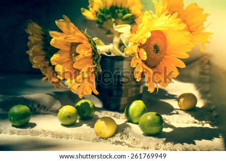 vintage Still life with sunflowers and lemons on the table - stock photo