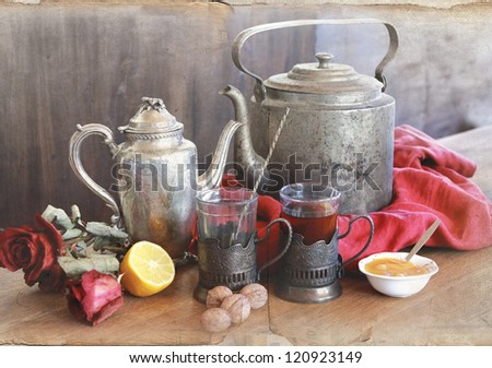 vintage still life with teapot's, cups in glass-holders, lemon and honey - stock photo