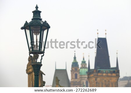 Vintage street lamp located on the Charles bridge and old medieval towers in the background, Prague, Czech Republic