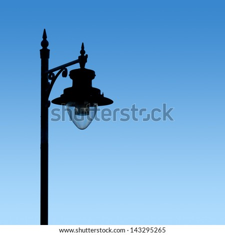 Vintage street lamp; silhouetted against graduated blue sky; excellent copy space  - stock photo