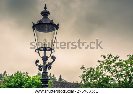 Vintage street lamp with a bulb in cloudy weather - stock photo
