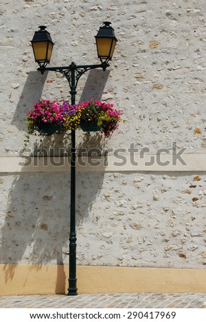 Vintage streetlight with yellow glass and hanging flower pots. Street of medieval town in France. - stock photo