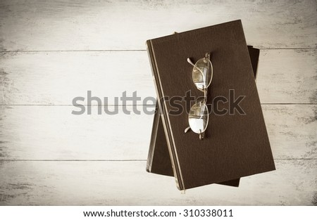 Vintage style background of old book with eyeglasses - stock photo