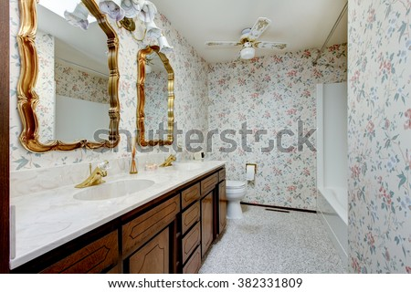 Vintage style bathroom with gold brimmed mirrors, and floral patterned wall paper. - stock photo