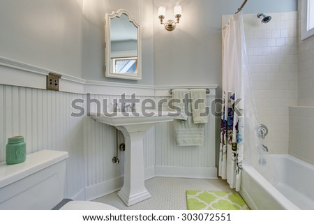 Vintage style bathroom with white interior, and decorative shower curtain. - stock photo