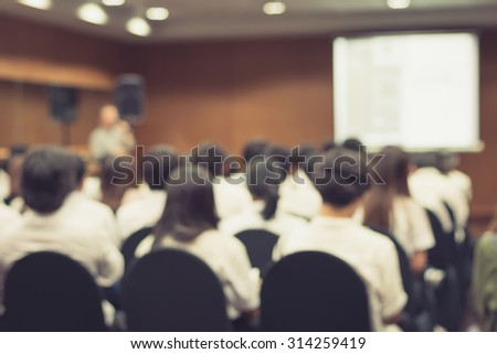 Vintage style blurred abstract background of university students sitting in a lecture room with teacher in front of the class with white projector slide screen: Blurry view from back of the classroom  - stock photo