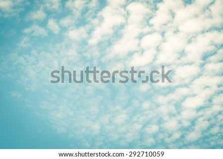 Vintage style blurred nature background of sky and soft scattered moving clouds with empty space in the air in the corner : Holiday lovely puffy clouds with summer sky in retro style   - stock photo