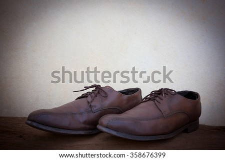 vintage style Brown leather shoes, put on the old wooden floor, vintage , still lift,selective focus