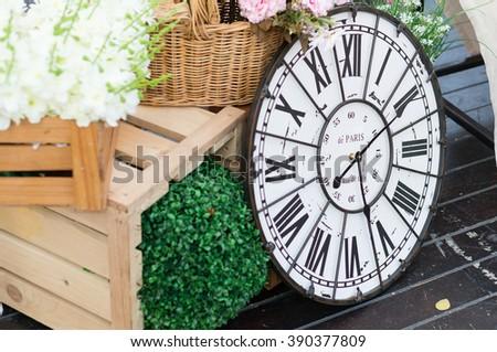 Vintage style clock on the dark brown wooden floor. Selective focus. - stock photo