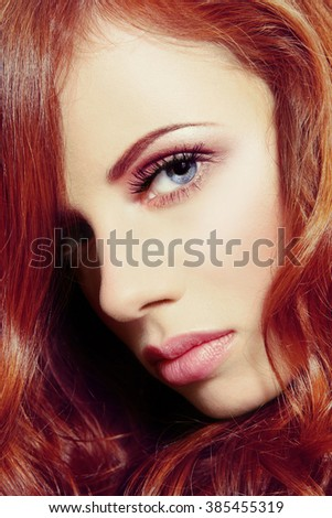 Vintage style close-up portrait of young beautiful girl with long curly red hair