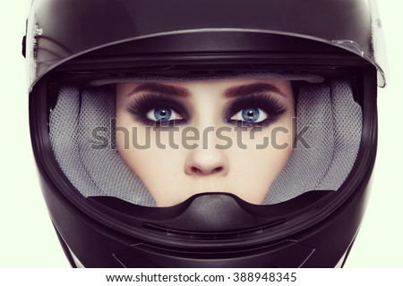 Vintage style close-up portrait of young beautiful woman with stylish make-up in biker helmet - stock photo