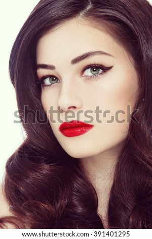 Vintage style close-up portrait of young beautiful woman with winged eyes make-up, red lips and long curly hair - stock photo