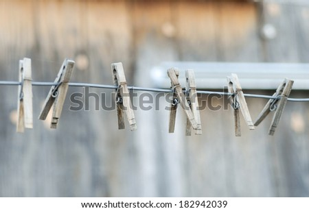 Vintage style clothespins on a metal wire line. - stock photo