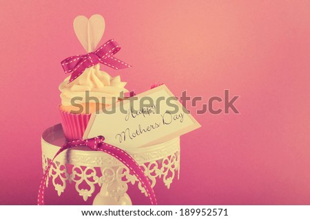 Vintage style Happy Mothers Day pink heart cupcake on white cupcake stand with greeting gift tag against a feminine pink background, with copy space for your text here.. - stock photo