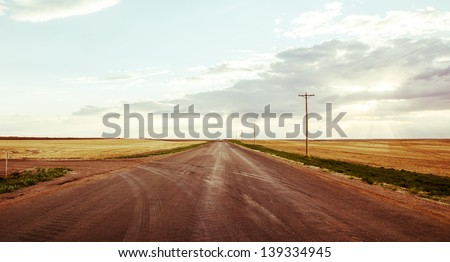 Vintage style image of a road on the prairies in the summer. - stock photo