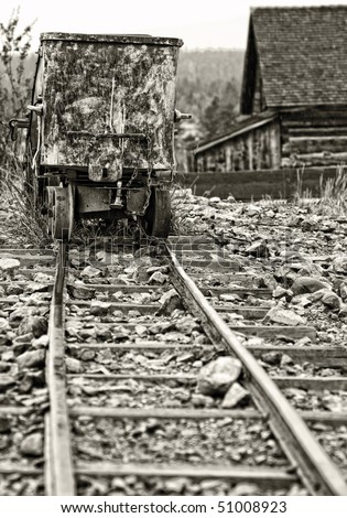 Vintage-style image of an authentic old mining ore cart and tracks in a historical western American ghost town - monotone tint and focus point on cart. - stock photo