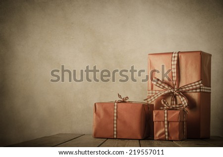Vintage style image of gifts wrapped in paper and tied with gingham ribbon on a wood planked table with parchment background and vignette.  brown and coral tones with copy space to left and above. - stock photo