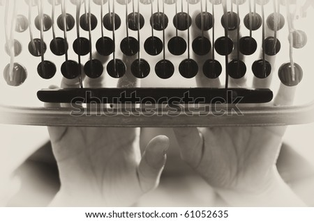vintage style image of old typewriter machine in action - stock photo