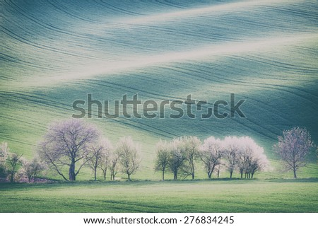 Vintage style image of rolling hills, trees and green grass fields - stock photo