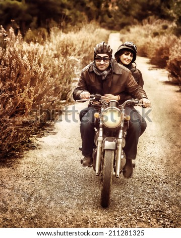 Vintage style image of two happy bikers riding on the road, active family enjoying journey on luxury extreme transport, freedom concept - stock photo