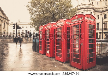 Vintage style image of typical red telephone booths on rainy street in London