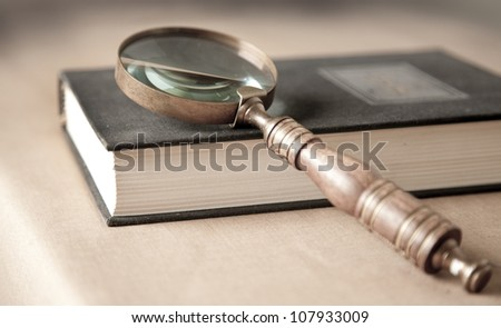 Vintage style magnifying glass on a book - stock photo
