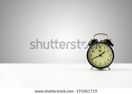 Vintage style metal alarm clock with bells standing on a white counter against a graduated grey background with central highlight and plenty of copyspace.