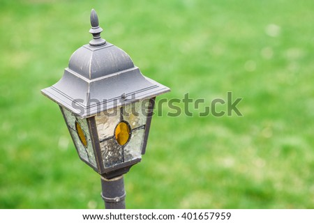 Vintage style metal and glass garden lamp with yellow painted tiffany glass sides on blurred green grass background