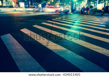 Vintage style - Night view of Crosswalk and pedestrian at modern city zebra crossing street in rainy day. Blur abstract. - stock photo