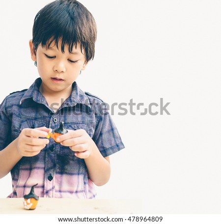 Vintage style of Asian lovely boy is playing Halloween clay happily