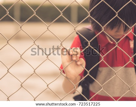 Vintage style of sad boy behind fence mesh netting. Emotions concept - sadness, sorrow, melancholy.