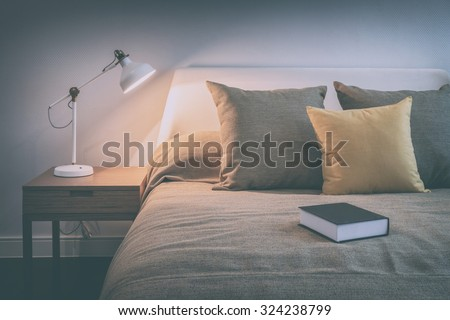vintage style photo of cozy bedroom interior with book and reading lamp on bedside table - stock photo