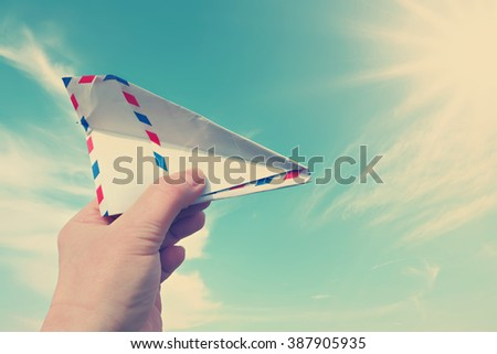 Vintage style photo of hand throwing  a paper plane (made of Post envelope) against beautiful blue sunny sky - stock photo