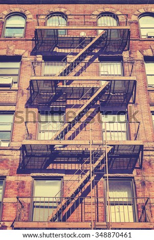 Vintage style photo of New York building with fire escape ladders, USA. - stock photo