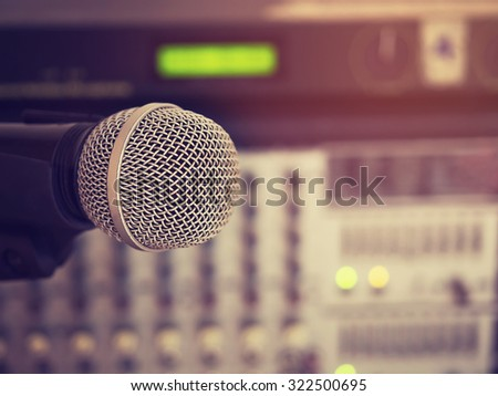 Vintage style photo of the microphone in a recording studio or concert hall with amplifier equipment in out of focus background. : Filtered process. - stock photo