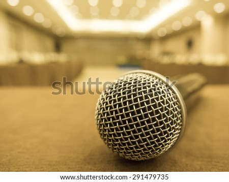 Vintage style photo of the microphone in hall or conference room with de focused bokeh lights in background. Concept for Business Conference. - stock photo