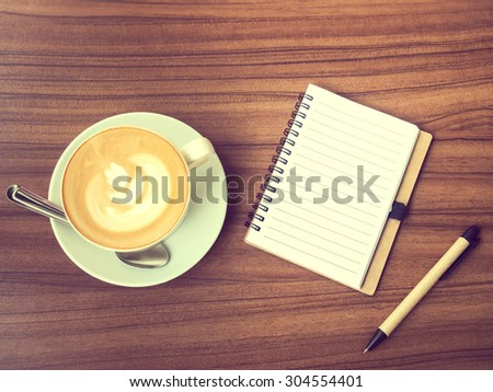 Vintage style photo of the workspace with coffee cup has flower pattern on top made from milk foam, open notebook  paper and pen on old modern wooden table. - stock photo