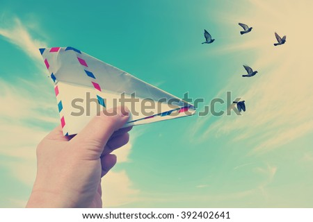 Vintage style photo with hand throwing a paper plane (made of Post envelope) and the flying pigeons against beautiful blue sunny sky - stock photo