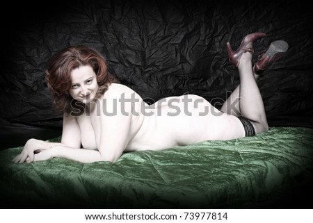 Vintage style picture of a overweight woman on a luxury green blanket. - stock photo
