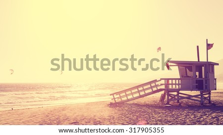 Vintage style picture of lifeguard tower at sunset in Malibu, lens flare effect, USA. - stock photo