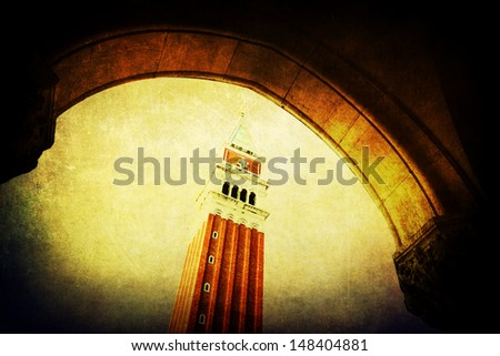 vintage style picture of the Campanile in Venice seen through an arch of the Doge's Palace - stock photo