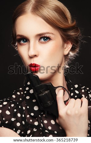 Vintage style portrait of beautiful young woman with revolver in her hand - stock photo