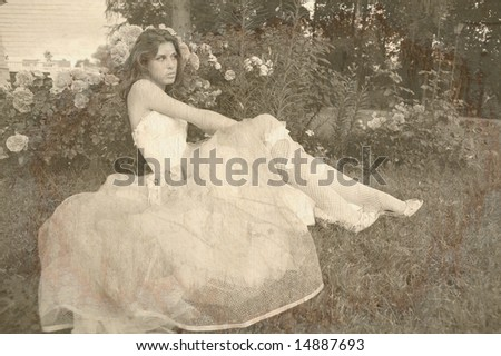 vintage style portrait of the beautiful girl in white gown on background of the rosebush, imitation of the old photography - stock photo