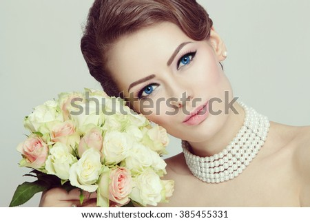 Vintage style portrait of young beautiful bride with stylish make-up and hairdo holding bouquet  - stock photo