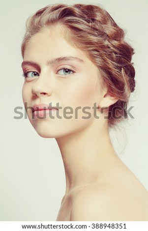 Vintage style portrait of young beautiful smiling healthy girl with clean make-up and braids