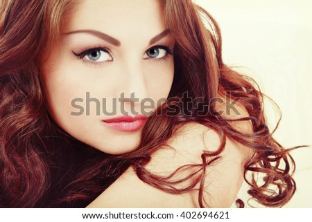 Vintage style portrait of young beautiful woman with eyebrows tattoo and long curly hair